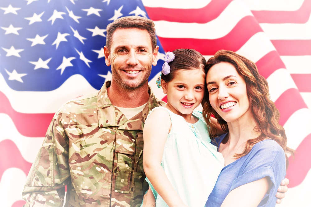 Soldier reunited with family against rippled us flag.jpeg